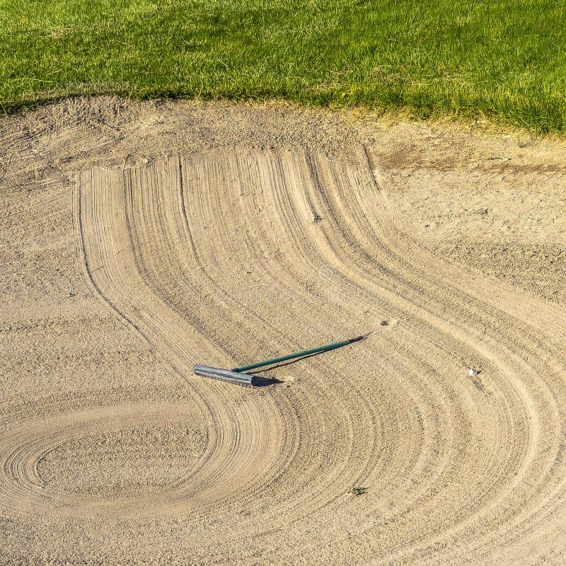 方形的框架关闭高尔夫球场与犁耙创造的一个圆样式的沙子地堡 图库摄影