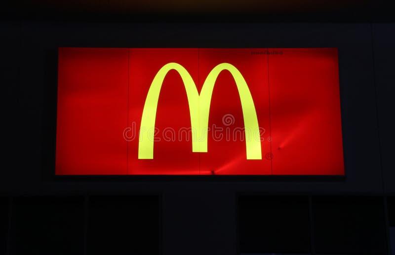 方形的灯箱麦克唐纳` s商标在特易购莲花廉价商店前面的晚上 免版税库存照片