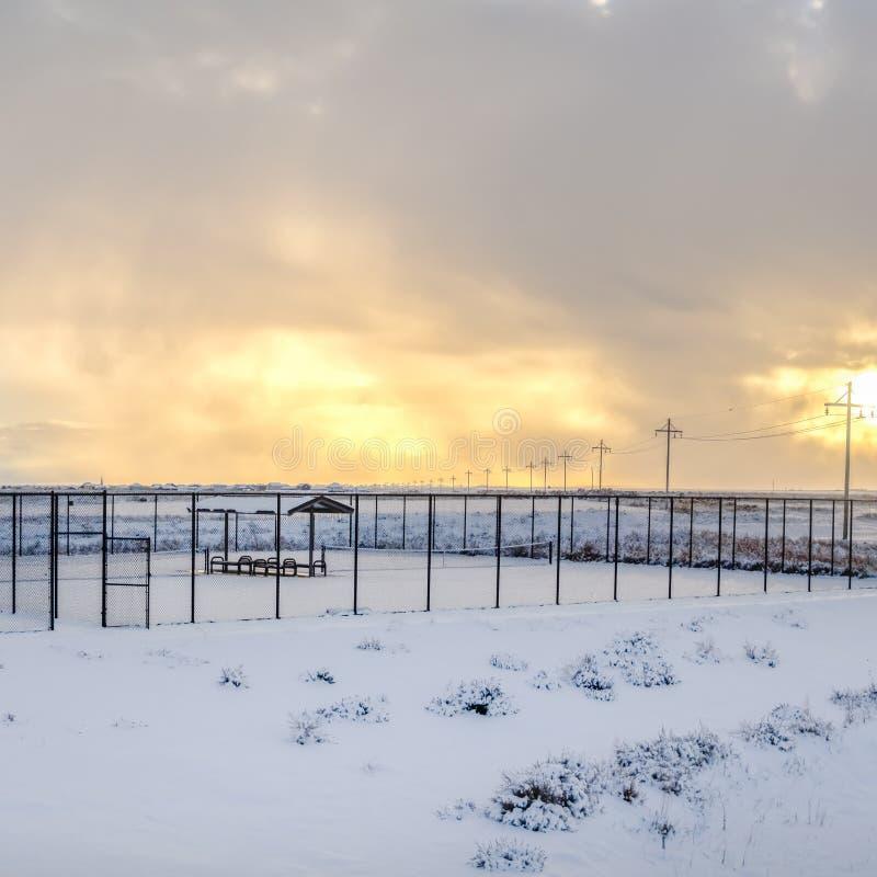 方形的网球场在链节篱芭里面和覆盖与雪在冬天 库存图片