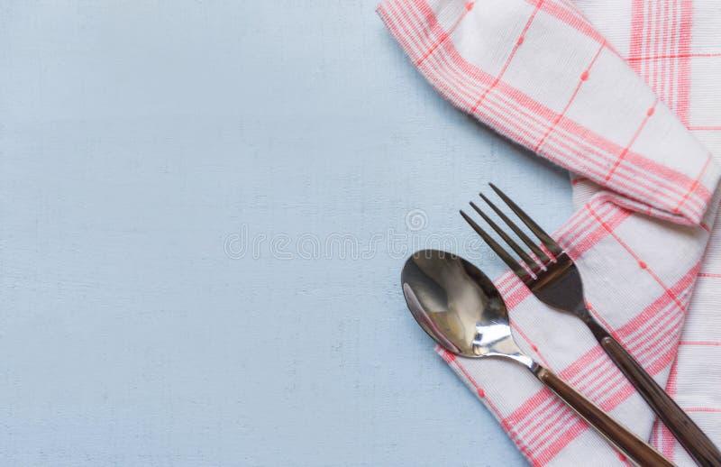 方格的与叉子的桌布红色在饭桌-家庭用亚麻布的andwhite和匙子 库存图片