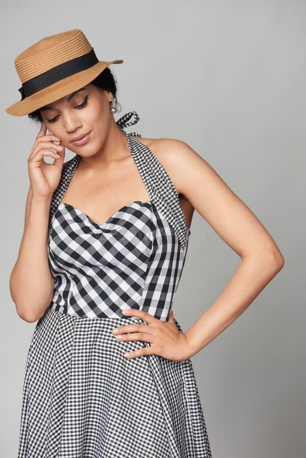方格的夏天礼服和canotier草帽的沉思混合的族种妇女 免版税库存图片