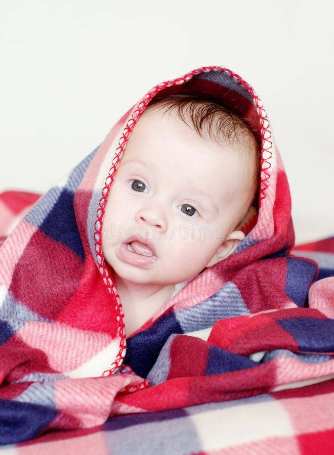 方格的格子花呢披肩盖的可爱的婴孩 免版税库存图片