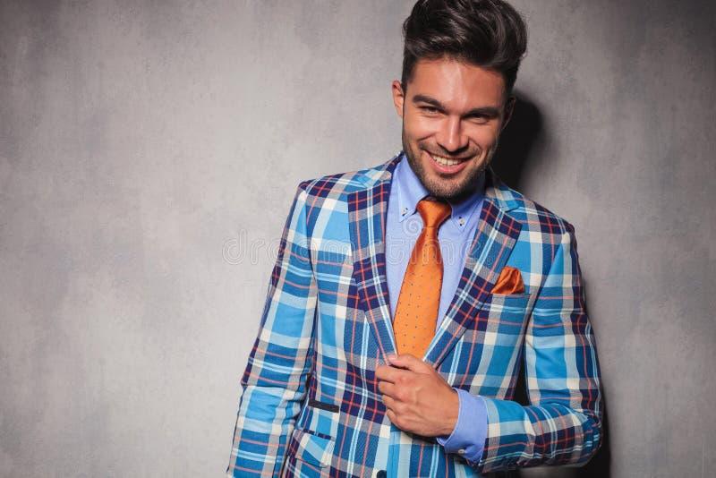方格的衣服和橙色领带的笑的年轻人 免版税图库摄影