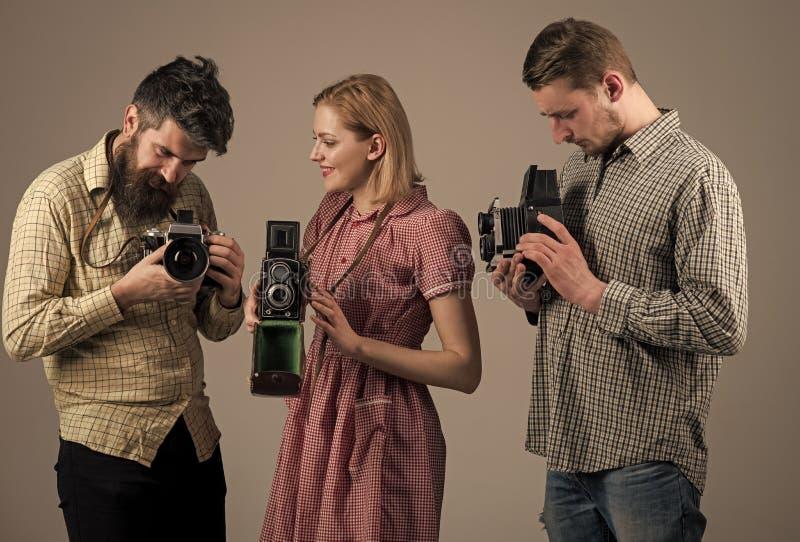 方格的衣裳的,减速火箭的样式人 葡萄酒摄影概念 繁忙的摄影师公司有老照相机的 库存图片