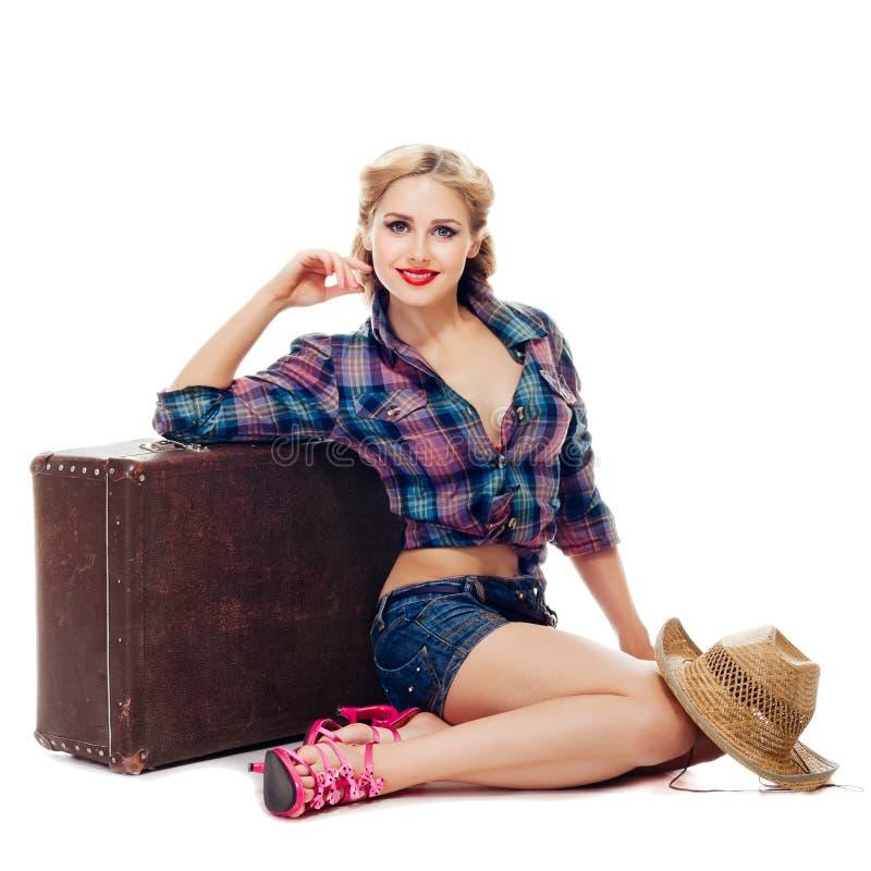 方格的衬衣和牛仔布短裤的美丽的白肤金发的女孩在有草帽和微笑的一个老手提箱附近坐 图库摄影
