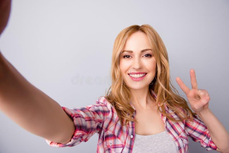 方格的衬衣的年轻美丽的妇女采取的自画象 免版税库存图片