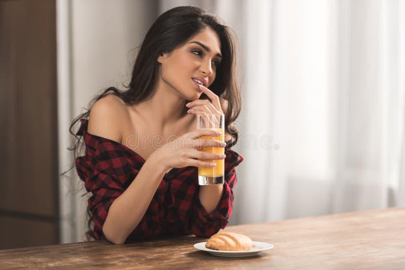 方格的衬衣的性感的女孩吃新月形面包和喝橙汁的 图库摄影