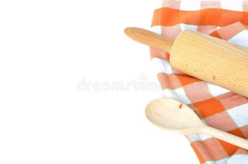 方格的洗碗布、木在白色隔绝的滚针和匙子 免版税库存图片