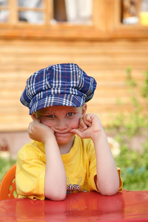 方格穿蓝衣的男孩的盖帽 库存图片