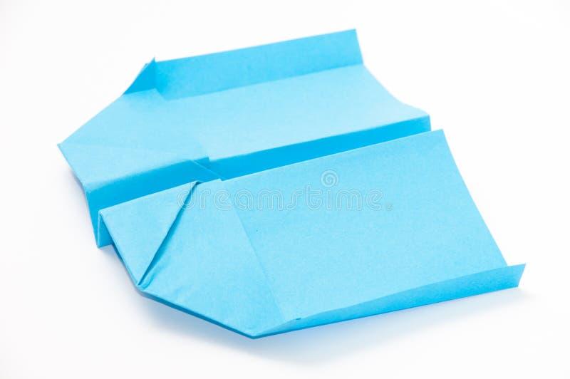 方格纸在白色背景的origami飞机 免版税库存图片