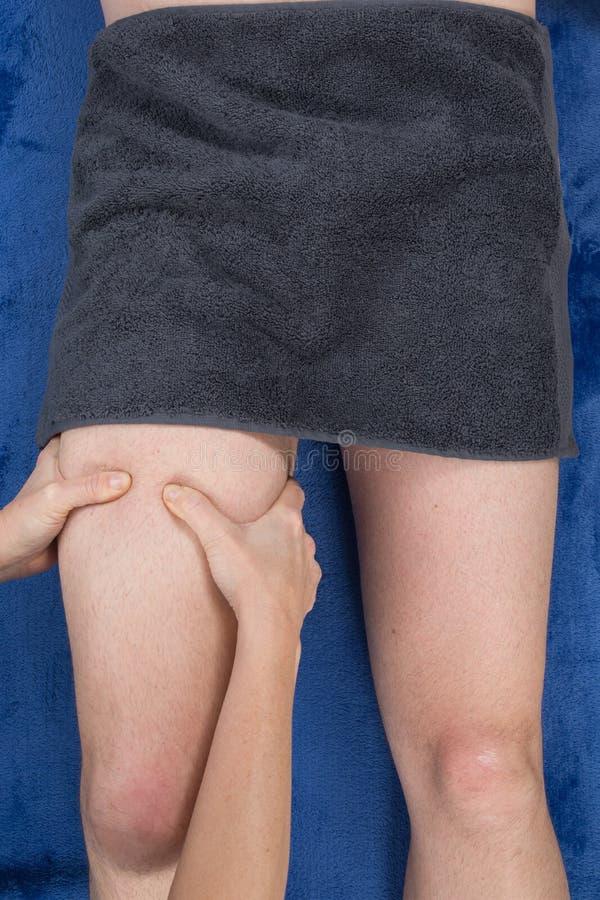 施加在男性腿筋的女性治疗师压力 免版税库存照片