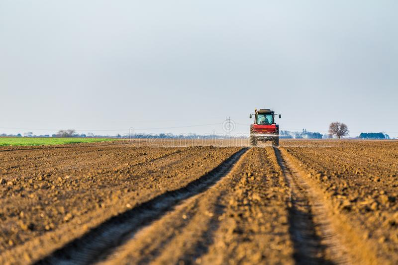 施肥有氮气的,磷,钾肥料的农夫耕地 库存照片