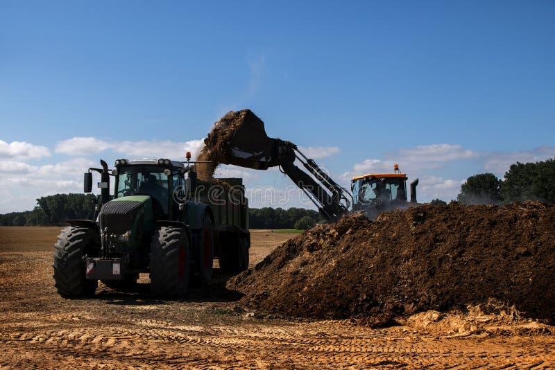 施肥领域,有铁锹积土肥料的挖掘机在t 免版税图库摄影
