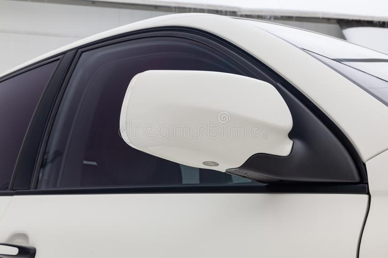 旁边左镜子的特写镜头有转弯信号车身在以后停放的街道上的白色SUV的中继器和窗口的 免版税库存图片
