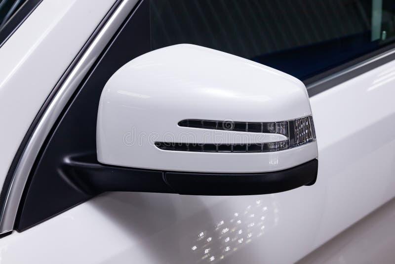旁边左镜子的特写镜头有转弯信号车身在以后停放的街道上的白色SUV的中继器和窗口的 库存照片