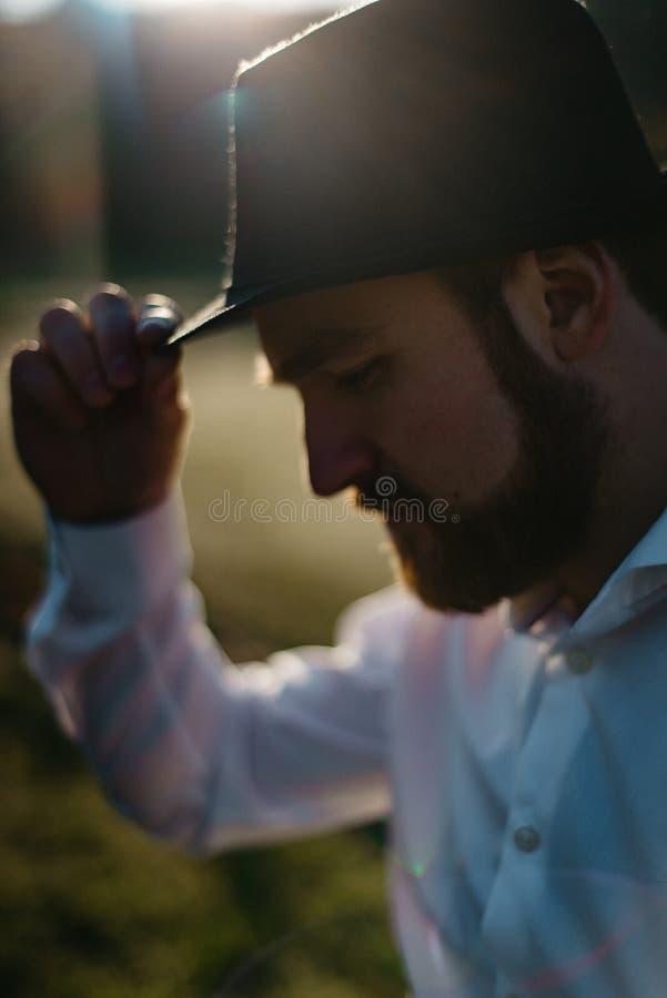 旁边时髦的英俊的人的特写镜头室外画象有接触他的黑帽会议和看下来在的胡子的 免版税库存照片