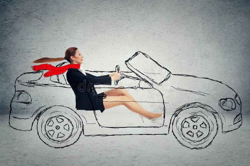 旁边驾驶汽车的外形可爱的妇女 免版税图库摄影