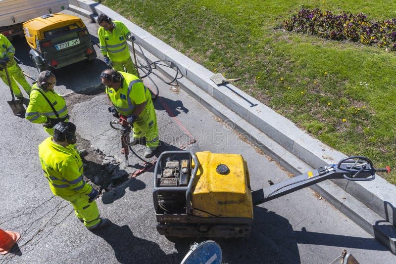 旅团路工作者修理沥青覆盖物 免版税库存照片