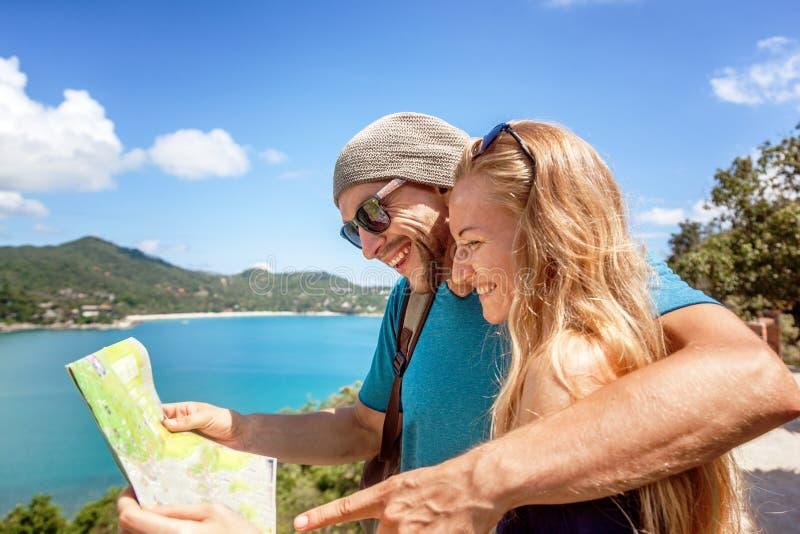 旅客一对年轻夫妇在地图,海和美丽看 免版税库存图片