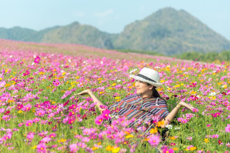 旅客亚裔妇女在美丽的开花的波斯菊花园里放松和自由 免版税库存照片