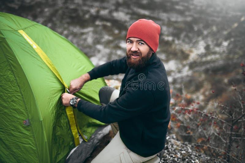 旅客人顶上的射击有胡子沥青帐篷露营齿轮的室外在山 男性远足在moutain 旅行,生活方式 库存照片