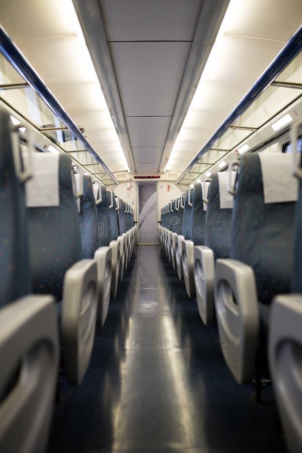 旅客列车汽车教练或支架的亦称空的内部 没人住的位子和折叠式小桌行在经济 库存图片