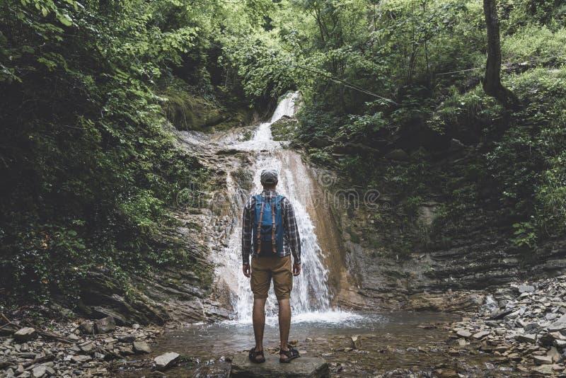 旅客到达了目的地并且享受瀑布看法,背面图沉思冒险概念 免版税库存照片
