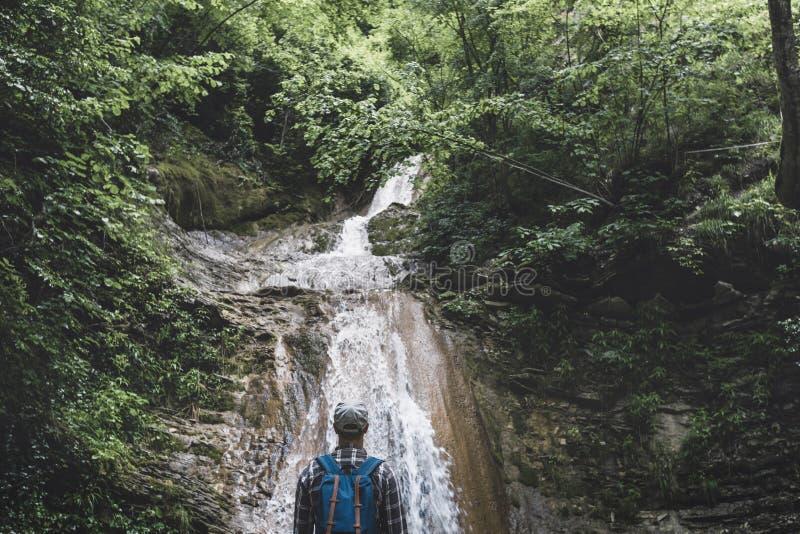 旅客到达了目的地并且享受瀑布看法,远足概念的背面图旅行 库存照片