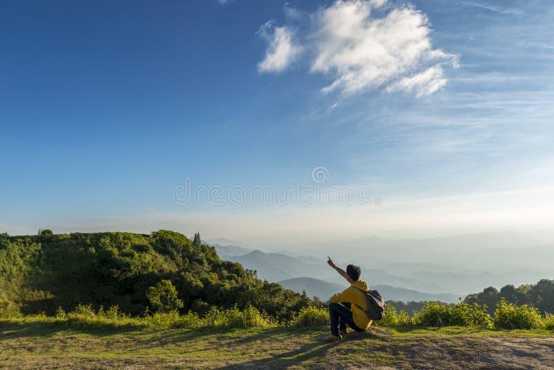 旅客在岩石的人选址有山背景 免版税库存图片
