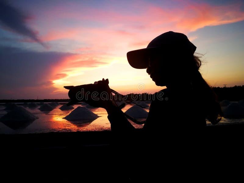 旅客在晚上为在盐领域的盐照相,当铲起盐入堆时在采摘前由商店决定 免版税图库摄影