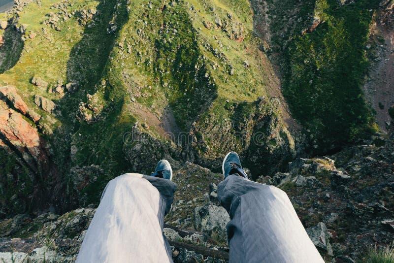 旅客坐在峭壁边缘 人脚在山风景的背景中 冒险和生活方式的概念 免版税图库摄影