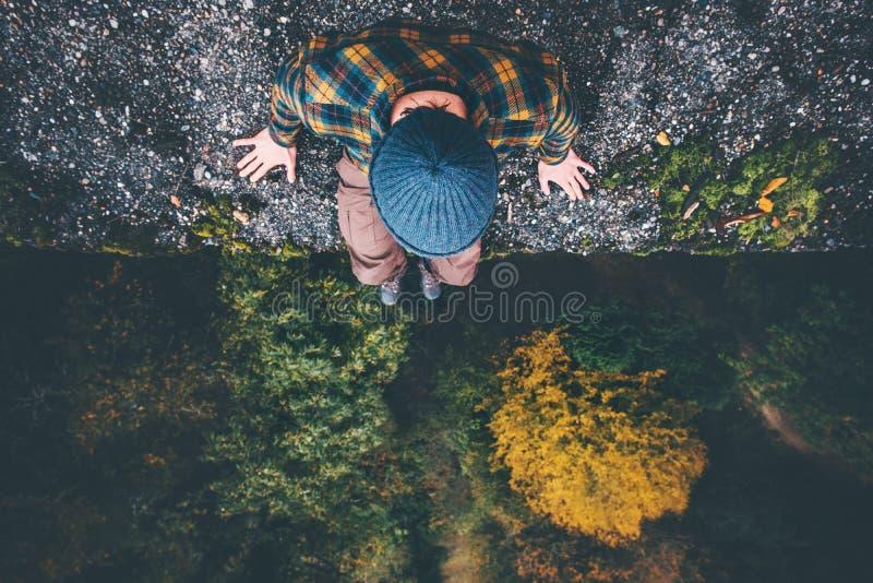 旅客坐峭壁桥梁边缘有森林鸟瞰图 免版税库存照片