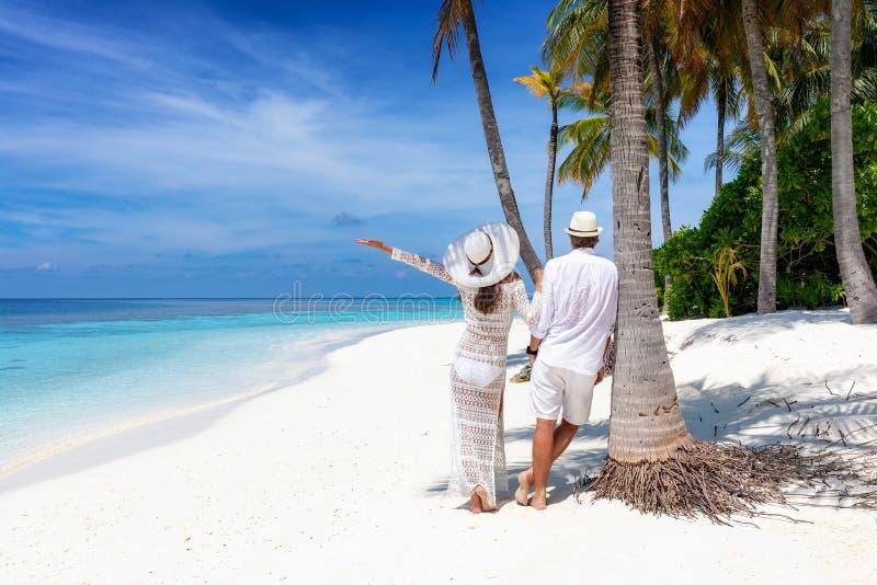 旅客夫妇在一个美丽,热带海滩站立 免版税图库摄影