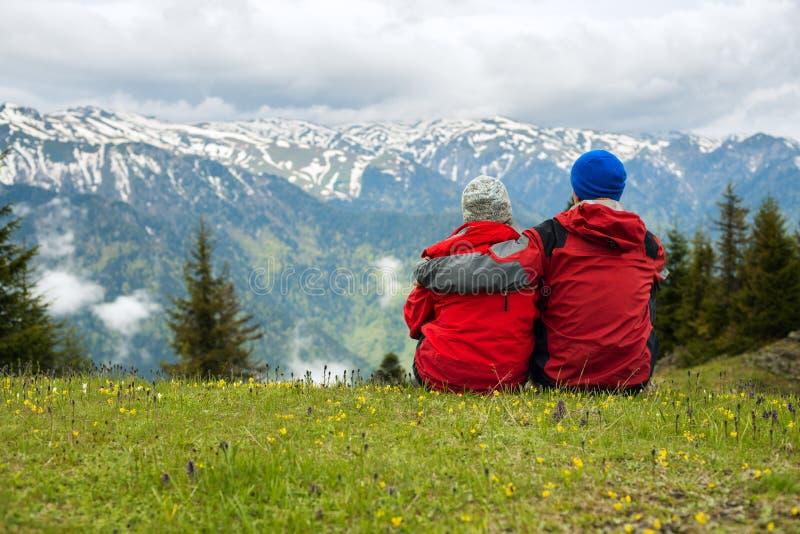 旅客夫妇坐,拥抱在一个高山草甸 免版税图库摄影