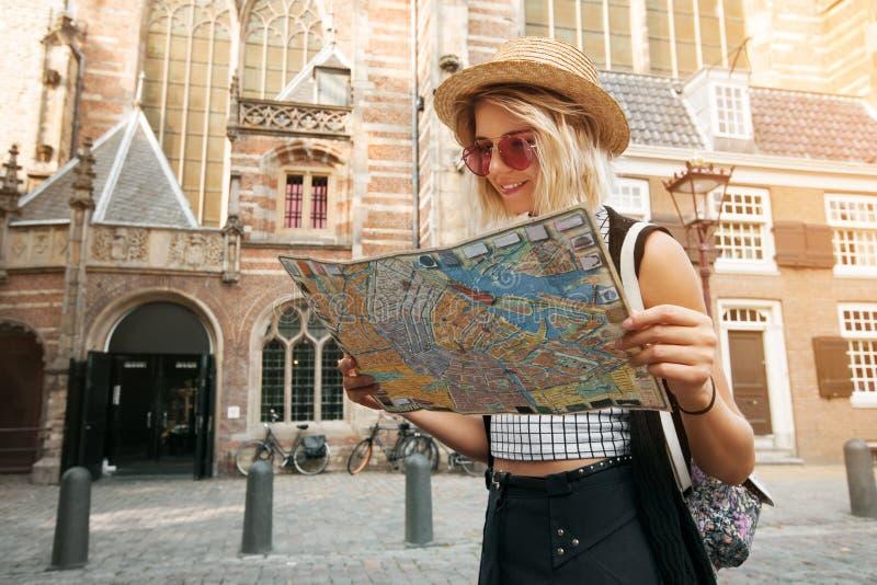 旅客女孩举行和神色在阿姆斯特丹映射 搜寻在地图的行家游人正确的方向,生活方式概念冒险 免版税库存图片