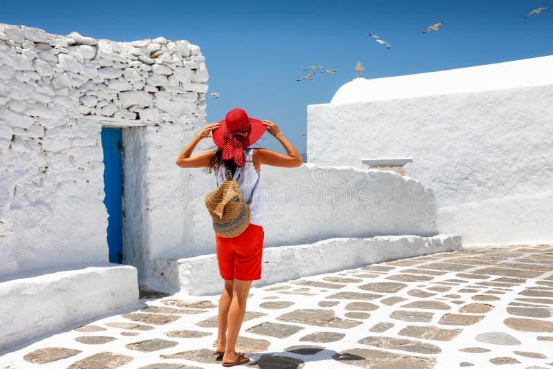 旅客妇女享受在米科诺斯岛,海岛希腊的经典希腊Cycladic建筑学 免版税库存照片