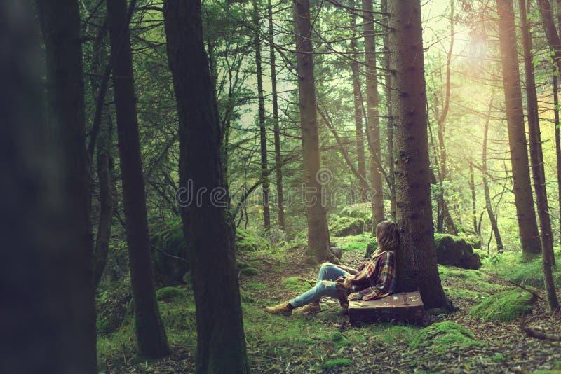 旅客妇女在一个神奇和超现实的森林里休息 免版税库存照片