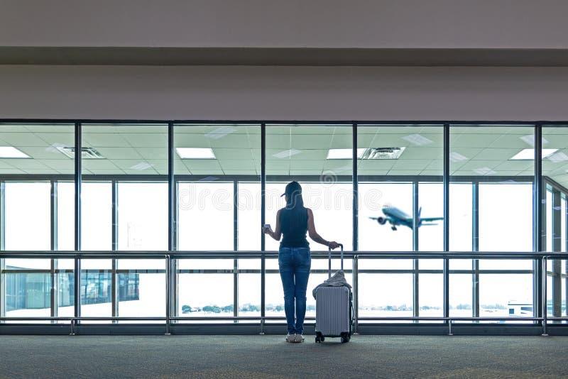 旅客妇女计划并且挑运看飞机在机场玻璃窗,亚洲旅游举行袋子和等待在行李附近  库存图片