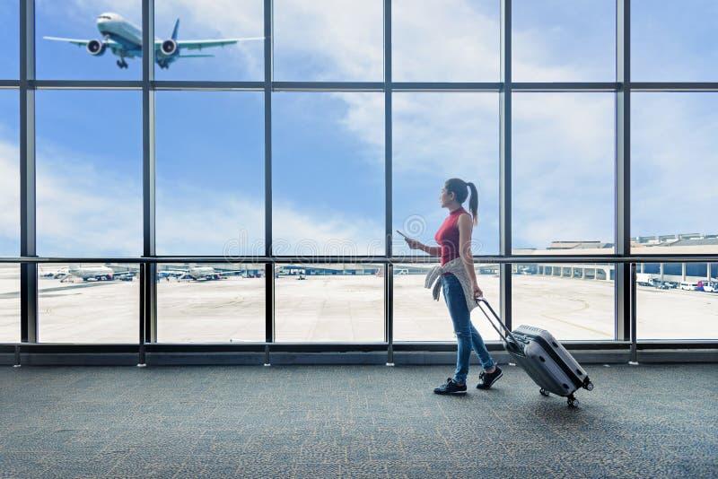 旅客妇女计划并且挑运看飞机在机场玻璃窗 亚洲旅游举行袋子 免版税库存图片