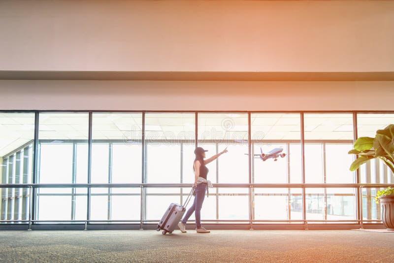 旅客妇女计划,并且背包看见飞机在机场玻璃窗,女孩旅游举行袋子和等待在h的行李附近 免版税库存图片