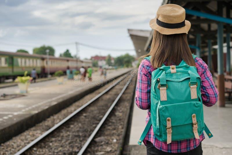 旅客妇女走和等待在铁路平台,太阳光火光训练 免版税库存图片