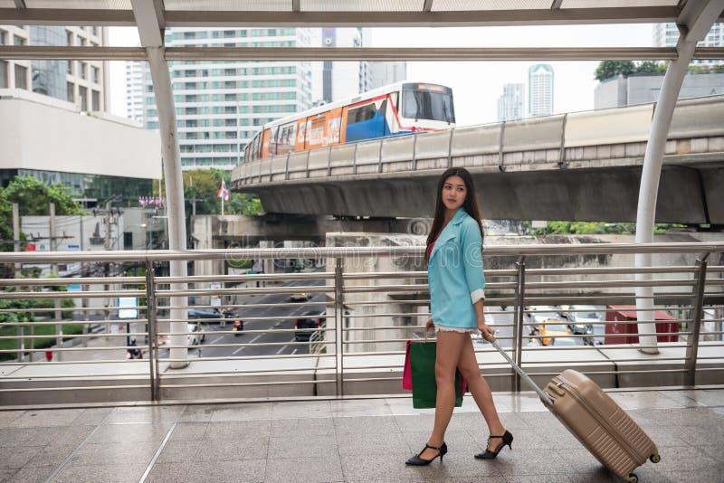 旅客拉扯行李和购物在城市 免版税库存照片