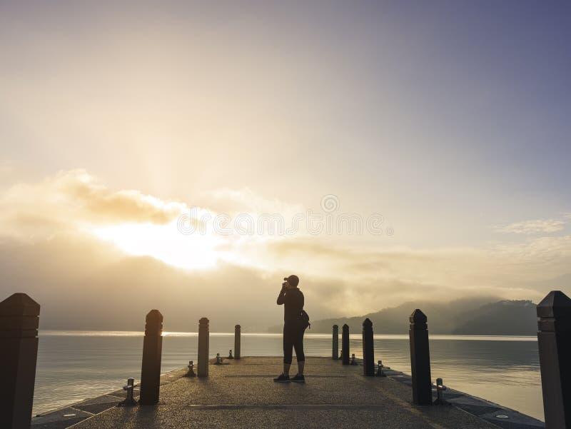 旅客拍在码头湖室外日出自然探险家的照片 免版税库存图片