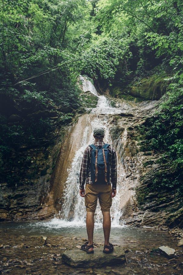 旅客探险家在岩石站立并且享受狂放的自然,背面图看法  远足冒险概念 库存照片