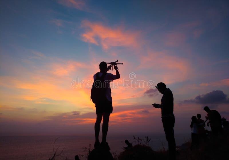 旅客控制直升机和拍摄五颜六色的日出剪影  人做空中照片和录影日落天空在是 免版税库存照片
