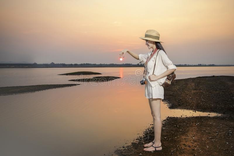 旅客放松在安静的湖的日落的穿戴便服 库存图片