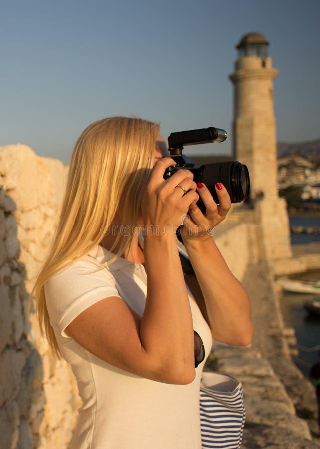 旅客有专业照相机的妇女摄影师采取罗希姆诺,克利特,希腊射击  库存照片