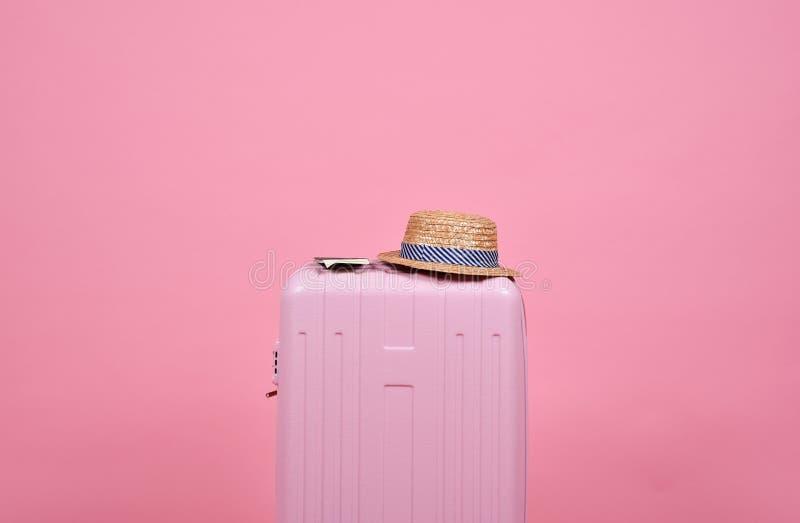 旅客桃红色手提箱和护照文件在桃红色背景、旅途和旅行 库存照片