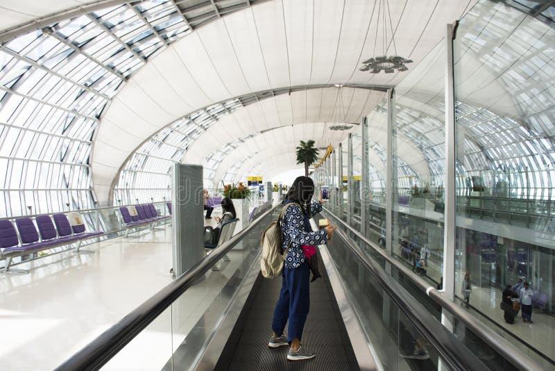 旅客泰国妇女用途智能手机在机场采取与票的照片和护照 库存照片