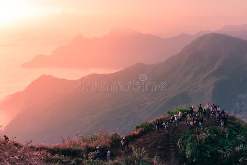 旅客站立在山顶部的小组看和夺取日出场面 免版税库存图片